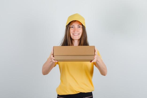Donna di consegna che tiene la scatola di cartone in maglietta gialla, pantaloni e cappello e che sembra allegra