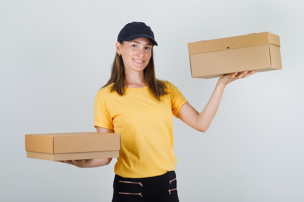 Доставщица держит картонные коробки в футболке, штанах и кепке и выглядит веселой