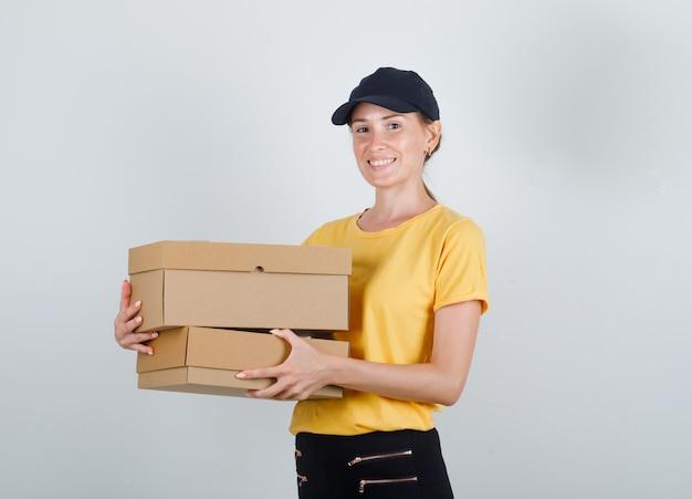 Доставщица держит картонные коробки в футболке, штанах и кепке и выглядит счастливой