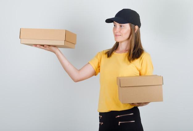Tシャツ、ズボン、帽子の段ボール箱を保持している配達の女性