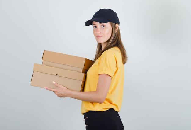 Donna di consegna che tiene scatole di cartone e sorridente in t-shirt, pantaloni e berretto.