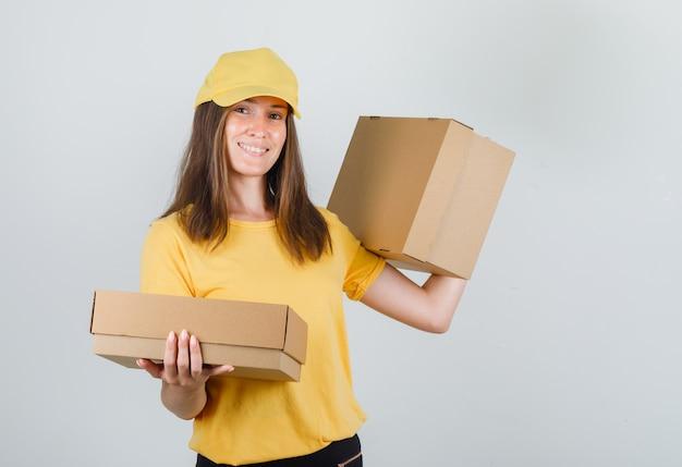 Donna di consegna che tiene le scatole di cartone e sorridente in maglietta, pantaloni e cappuccio gialli