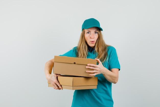Donna di consegna che tiene le scatole di cartone in maglietta, berretto e che sembra stupita