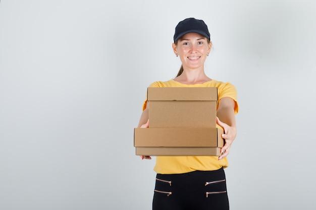 Donna di consegna che tiene le scatole di cartone in maglietta, pantaloni e berretto e che sembra allegra