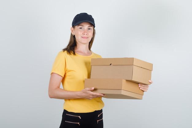 Donna di consegna che tiene scatole di cartone in t-shirt, pantaloni e berretto e sembra allegra