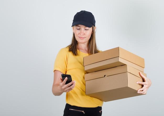 Donna di consegna che tiene scatole di cartone e utilizza lo smartphone in t-shirt, pantaloni e berretto