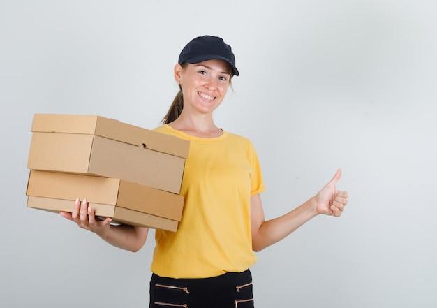 Donna di consegna che tiene le scatole di cartone con il pollice in su in maglietta, pantaloni, berretto e che sembra allegro