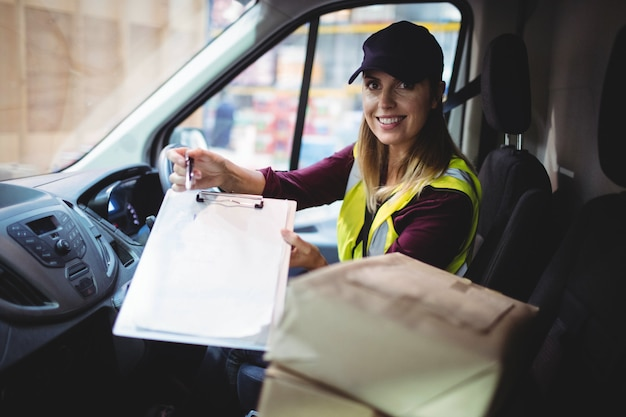 Delivery woman holding clipboard to camera with parcels on seat