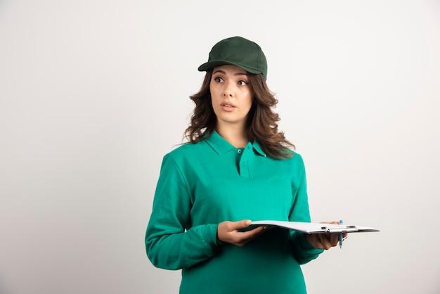 Женщина доставки, держащая доску сзажимом для бумаги на белом.