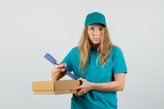 Donna di consegna che tiene appunti, penna, scatola di cartone in t-shirt, cappuccio