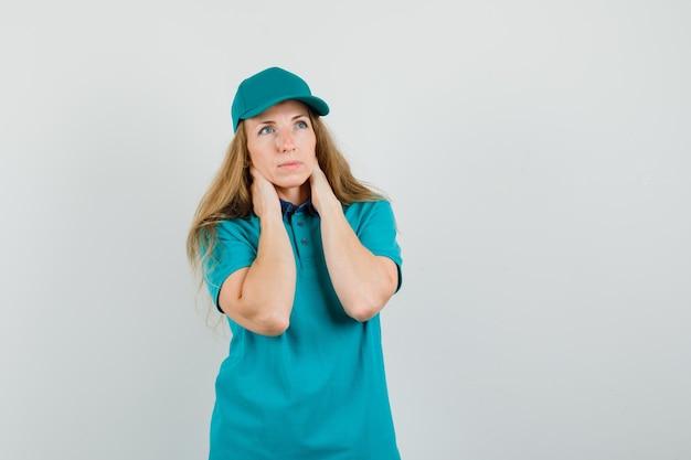 Donna di consegna tenendo le mani sul collo in t-shirt, berretto e guardando pensieroso.