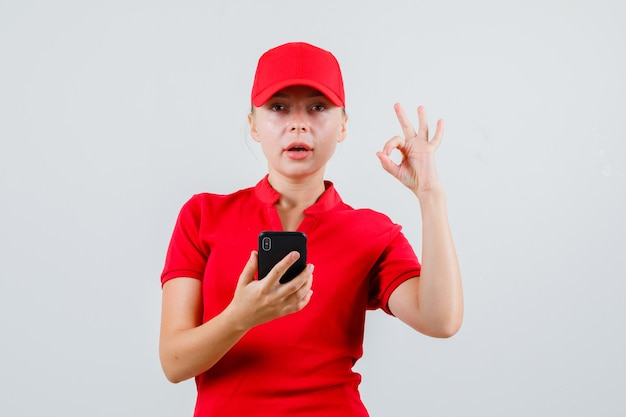 Delivery woman holding mobile phone with ok gesture in red t-shirt and cap and looking pleased