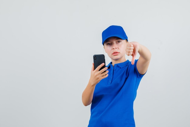 Delivery woman holding mobile phone with thumb down in blue t-shirt and cap