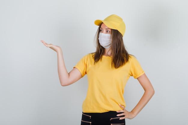 Tシャツ、ズボン、キャップ、マスクで開いた手のひらを保持している配達の女性