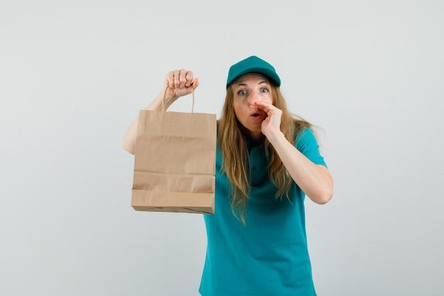 Женщина доставки держит бумажный пакет и рассказывает секрет в футболке, кепке и выглядит любопытно.