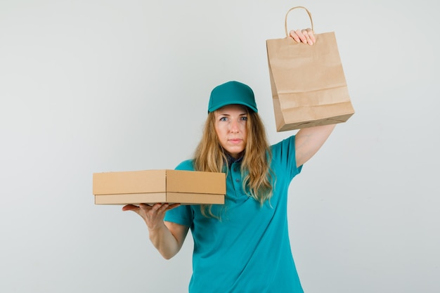 Delivery woman holding paper bag and cardboard box in t-shirt, cap