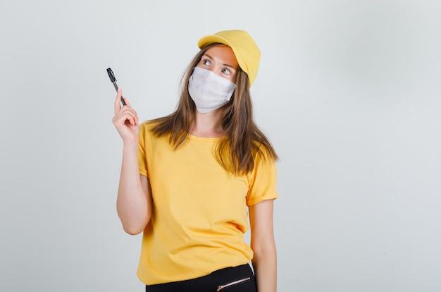 Женщина-доставщик держит ручку и смотрит вверх в футболке, штанах, кепке, маске и внимательно смотрит