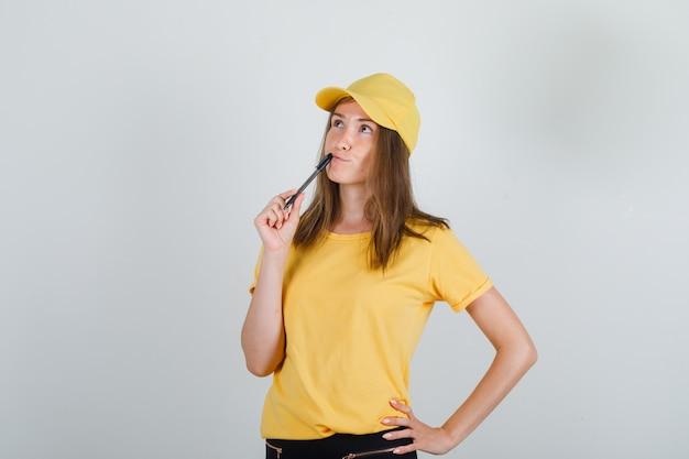 Доставка женщина держит ручку на губах в желтой футболке, штанах, кепке и выглядит задумчиво.