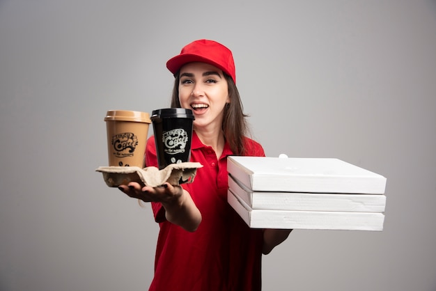 Женщина доставки, держащая пиццу и кофейные чашки на серой стене.
