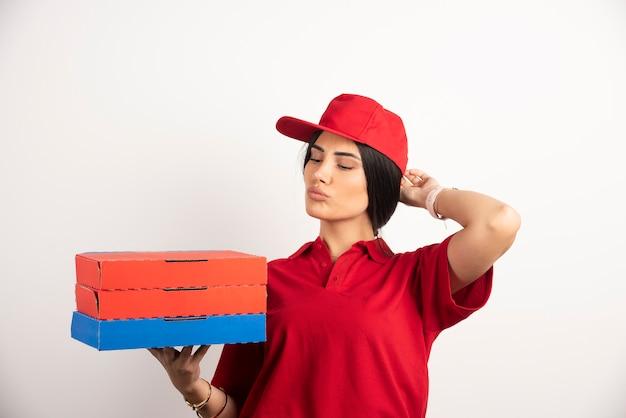 Donna di consegna che tiene scatole per pizza mentre inala l'aroma.