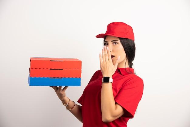 Donna di consegna tenendo la pizza con espressione scioccata.