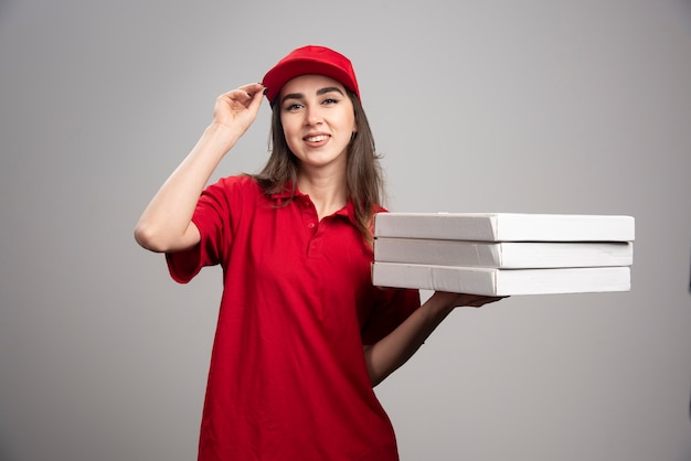 Delivery woman holding pizzas on gray wall.