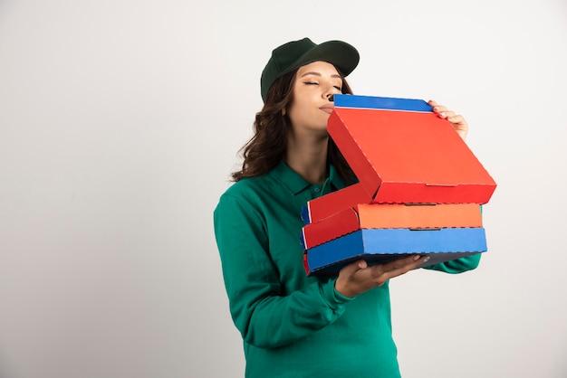 La donna delle consegne sente l'odore della pizza avidamente.