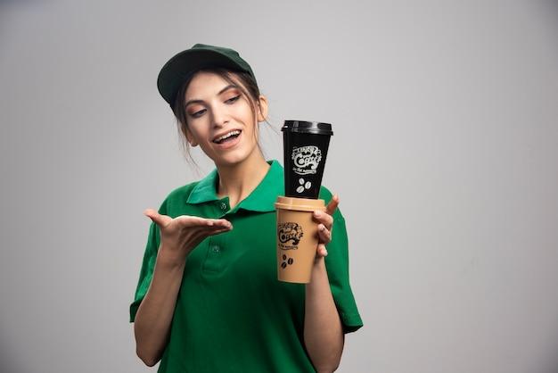 コーヒーカップを保持している緑の制服を着た配達の女性