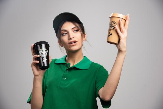 コーヒーカップを見て緑の制服を着た出産の女性