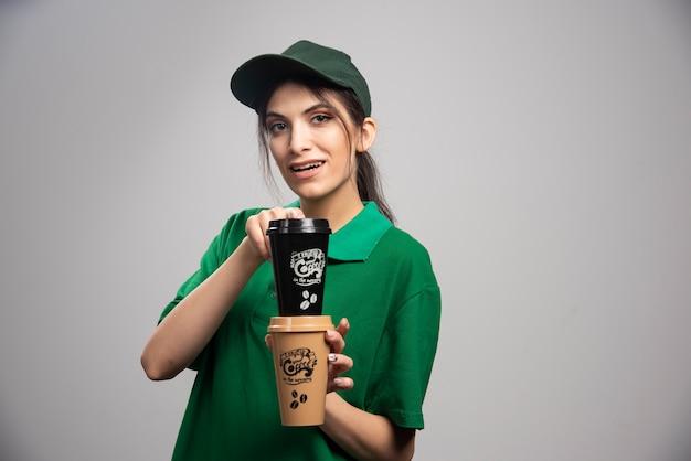 コーヒーカップでポーズをとって緑の制服を着た配達女性