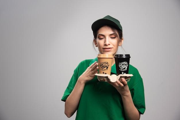 コーヒーのカップでポーズをとって緑の制服を着た出産の女性。