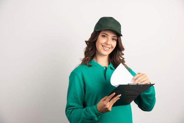 카메라에 웃 고 녹색 유니폼에 배달 여자입니다.