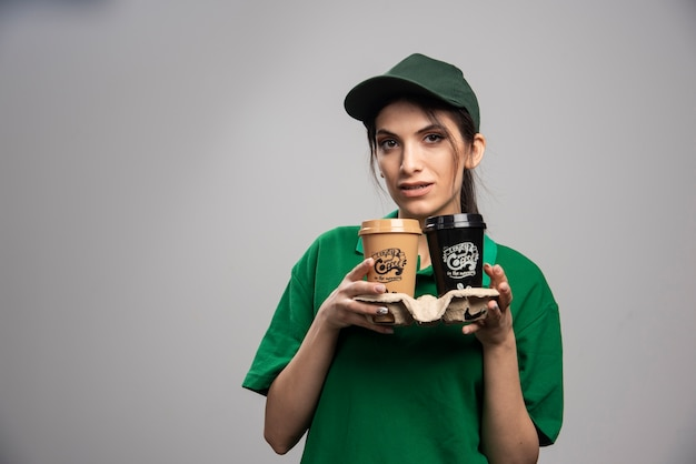 コーヒーのカップと立っている緑の制服を着た出産の女性。