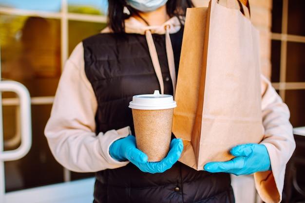 Доставка женщина в защитной маске и перчатках с мешком еды и кофе