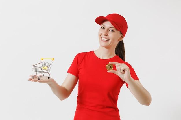 빨간 모자에 배달 여자, 흰색 배경에 고립 된 t-셔츠. 쇼핑, 비트코인, 황금색 금속 동전을 위해 슈퍼마켓 식료품 카트를 들고 있는 여성 택배. 광고 공간을 복사합니다.