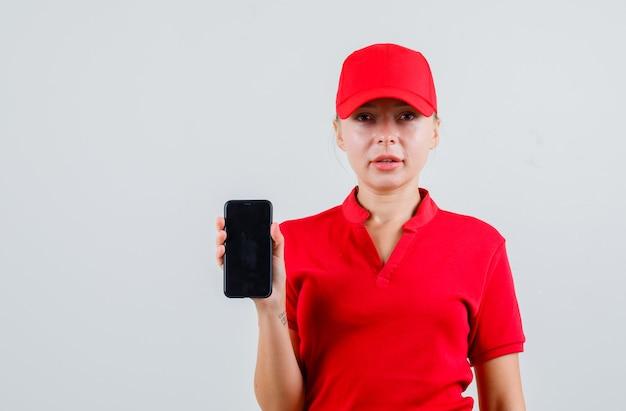 携帯電話を保持している赤いtシャツと帽子の配達の女性