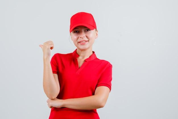Женщина-доставщик в красной футболке и кепке указывает назад и выглядит веселой