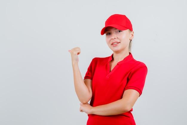 Женщина-доставщик в красной футболке и кепке, указывая большим пальцем назад и выглядит уверенно