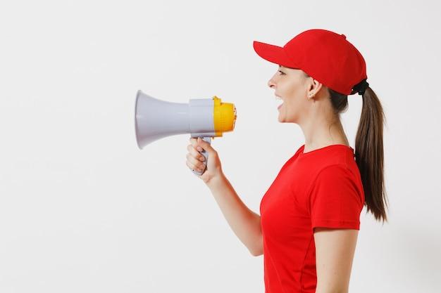 Женщина-доставщик в красной форме, изолированные на белом фоне. женский курьер в кепке, футболке кричит в мегафон горячих новостей. веселая девочка объявляет о распродаже со скидками. скопируйте место для рекламы. вид сбоку.