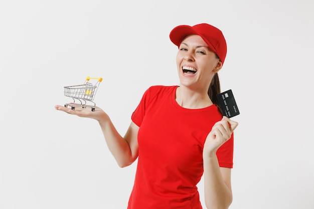 흰색 배경에 고립 된 빨간 제복을 입은 배달 여자. 모자를 쓴 여성 택배나 딜러, 쇼핑을 위한 슈퍼마켓 식료품 카트를 들고 있는 티셔츠, 신용 카드. 광고 공간을 복사합니다.