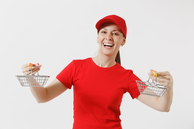 Женщина-доставщик в красной форме, изолированные на белом фоне. женский курьер или дилер в кепке, футболке, джинсах, держащей металлическую корзину для продуктов для покупок в супермаркете. скопируйте место для рекламы.