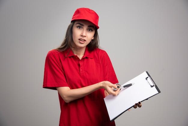 순서를 가리키는 빨간색 유니폼에 배달 여자.