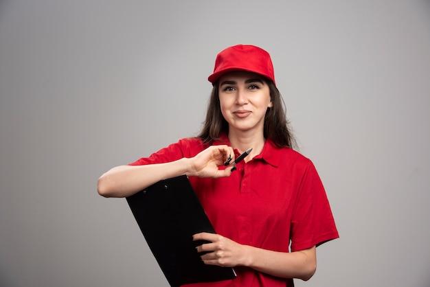Женщина-доставщик в красной форме позирует на серой стене.