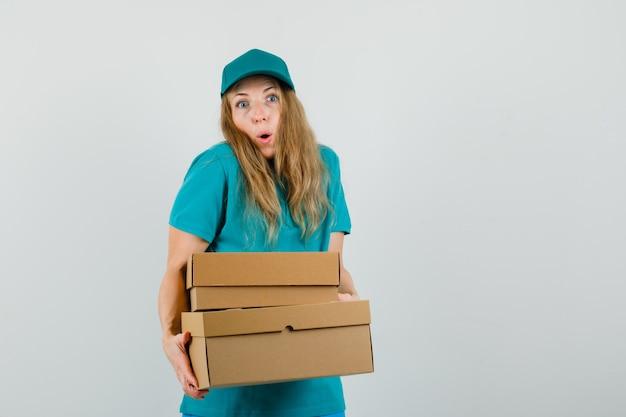 Женщина-доставщик в футболке, кепке держит картонные коробки и выглядит удивленно