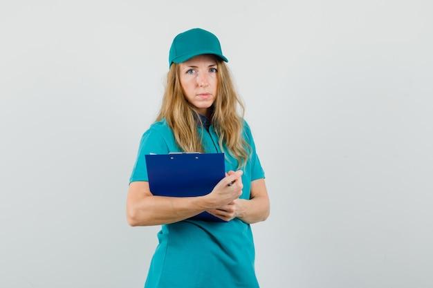 Tシャツ、クリップボードを押しながら賢明な探しているキャップの配達の女性