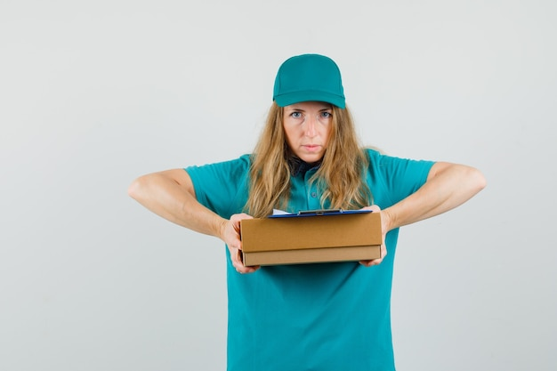 Tシャツ、段ボール箱にクリップボードを押しながら深刻な探しているキャップの配達の女性
