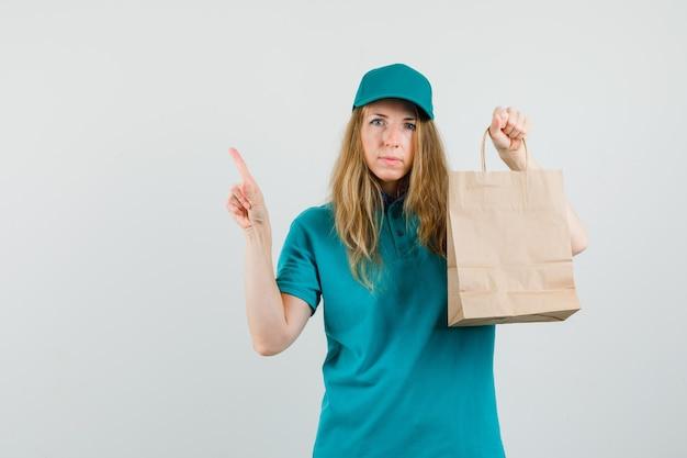 Женщина-доставщик в футболке, кепке держит бумажный пакет и указывает вверх
