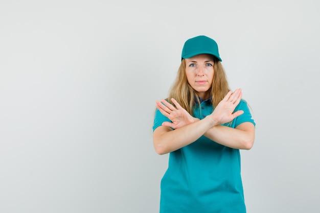 Tシャツの配達女性、拒否ジェスチャーを示し、穏やかに見えるキャップ