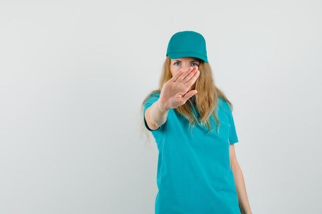 Доставщица в футболке, кепке показывает жест стоп и выглядит строго