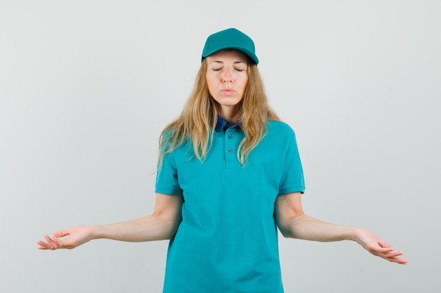 Tシャツの配達の女性、目を閉じて希望を探して手のひらを広げているキャップ